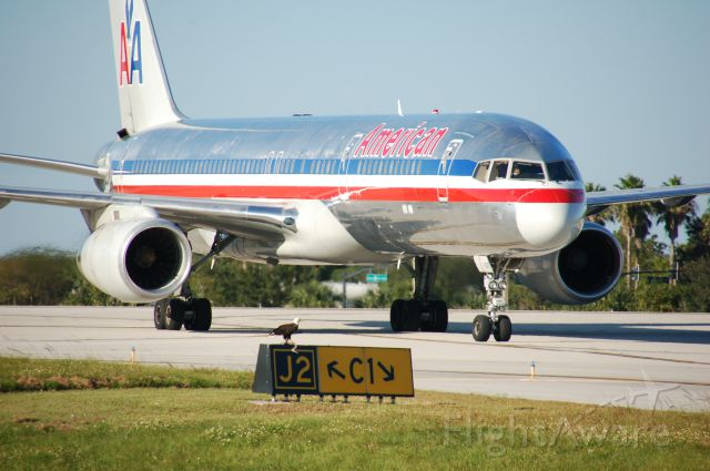 Boeing 757-200 (N639AA) - This American Bald Eagle had been flying around all day. When he landed on the taxiway sign as American Airlines was taxing in from KMIA. If you look close the eagle had just killed another bird.