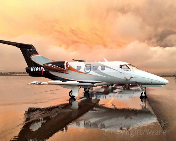 Embraer Phenom 100 (N161PL) - Phenom 100 on the very rare wet ramp in North Las Vegas under ominous skies.