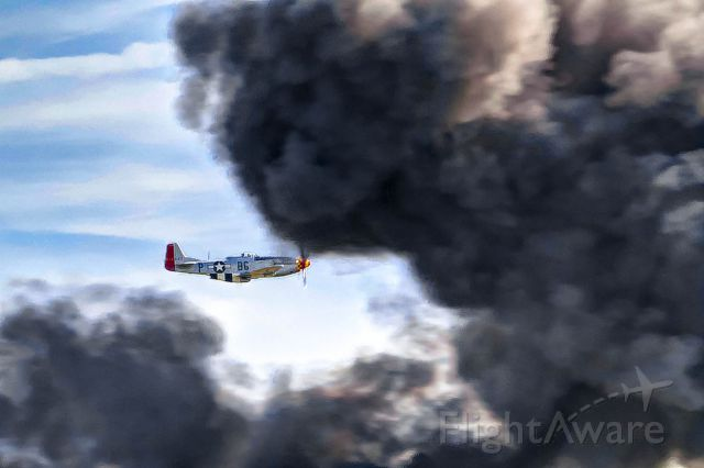"""North American P-51 Mustang (N551J) - The P-51 """"Gentleman Jim"""" flies through the smoke of an explosion at the Gathering of Mustangs and Legends airshow."""