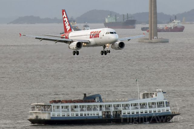Airbus A319 (PT-MZB) - Rare Composition of an Airplane going over the Ferry Boat.