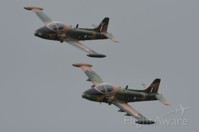 MULTIPLE — - BAC Strikemasters ZK-NTY (upper) and ZK-STR opening the first flying session at the NZ Warbirds Open Day on 22 November 2015. Conditions were overcast, just after a rain shower, with a strong blustery wind.
