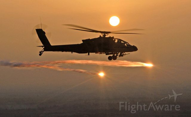 — — - An Ah-64 military helicopter firing.