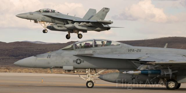 """McDonnell Douglas FA-18 Hornet (16-8385) - An E/A-18G Growler (168385) of the VAQ-142 """"Gray Wolves"""" comes past a waiting VFA-211 """"Fighting Checkmates"""" F/A-18F (166815) as it returns to NAS Fallon after participating in a training sortie. <br />This photo is the first pic of 168385 to be posted into FlightAware"""