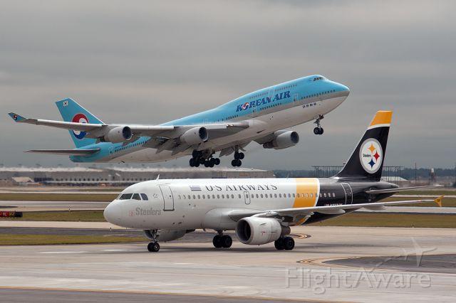 — — - A Korean Air B747-400 takes off as an US Airways A319 taxis to the gate. From South parking deck, H-J Atlanta International Airport.