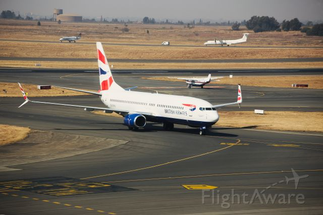 Boeing 737-800 (ZS-ZWG) - This Comair-Operated British Airways Boeing 737-8LD is about to turn off the taxiway to her parking bay after making the roughly 80 minute flight from Cape Town (FACT) to Johannesburg (FAOR) on Thursday, 1 August 2019. This picture was snapped at 11:43 in the morning, just on 15 minutes after touch-down on RWY 03R on a gloomy day. The sun popping through lit up her tail feathers quite nicely. *Click Full*