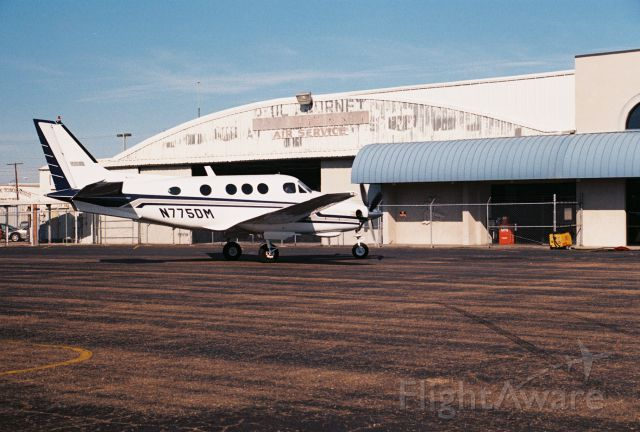 Beechcraft King Air 90 (N775DM) - Beechcraft King Air C90, msn LJ-764, manufactured in 1978 and photographed at KLFT, Lafayette Regional Airport. Parked at Paul Fournet Air Service FBO hangar. Photo taken circa year 2000 with a Canon 35mm camera.