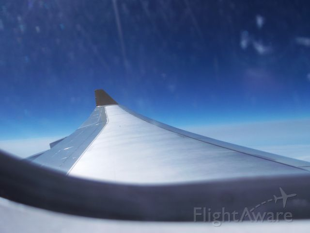 Airbus A330-200 (G-SMAN) - flying in economy over the Irish sea towards KSFB with slight turbulence and a scratched window
