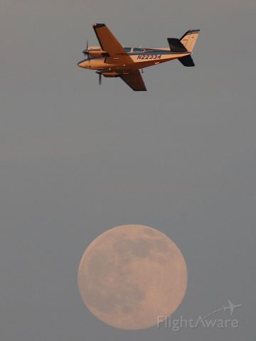 Beechcraft 55 Baron (N22334) - Beech Baron flying over the moon at sunset.