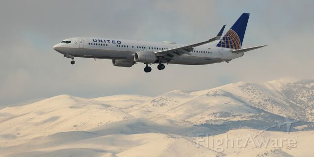 """Boeing 737-900 (N68817) - The snow-covered Sierra Nevada makes a """"cool"""" backdrop as this United B739 (N68817) approaches Reno Tahoe Internationals runway 16R to complete a flight from SFO."""
