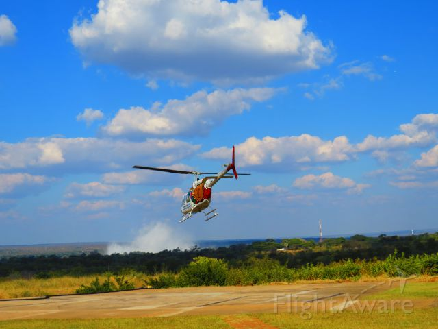 Bell JetRanger (Z-WLY) - Flying towards Victoria Falls, the column of spray in the distance.