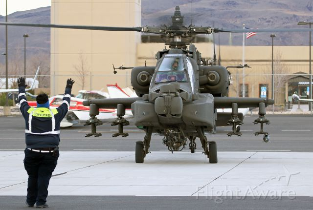 Boeing Longbow Apache — - As both pilots use their IHADSS (Integrated Helmet And Display Sighting System) to view him, an Atlantic Aviation agent marshals an Apache helicopter to a ramp parking position. However, since their IHADSS system allows them to aim that M230 Chain Gun cannon merely by looking at their target, perhaps that agent is not marshaling ... maybe he is surrendering.