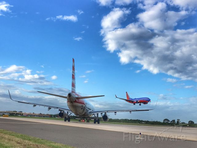 — — - American Airlines waiting to depart runway 1L, while Southwest arrives in TPA.