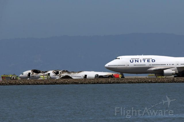 Boeing 777-200 (HL7742) - an united 747 stands near the sadly burnt aircraft HL7742 at SFO after it crash landed