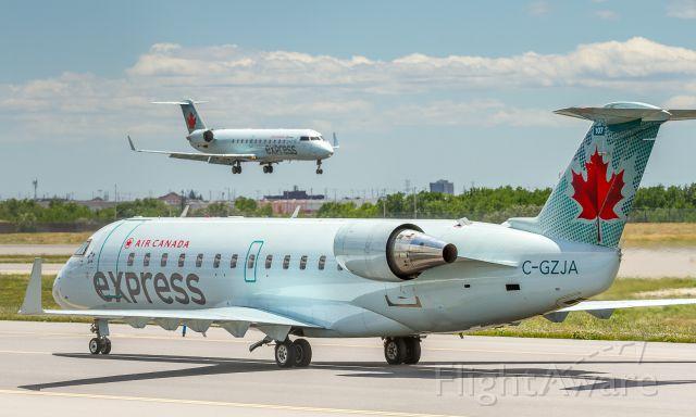 Canadair Regional Jet CRJ-200 (C-GZJA) - A company CRJ lands on runway 33L while this Air Georgian CRJ backtracks down the