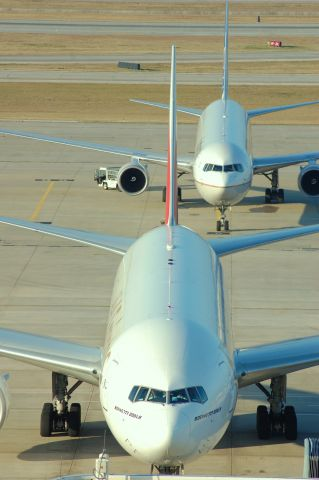 — — - Emirates 211 and a parked Boeing 767.