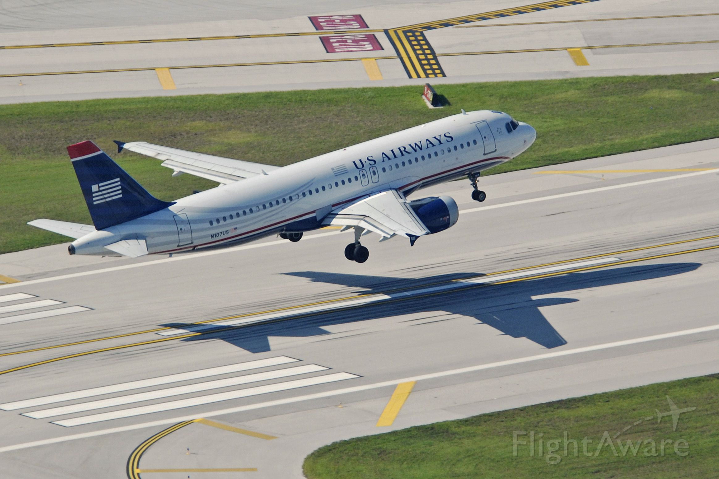 Airbus A320 (N107US) - Over the threshold for 27R at KFLL