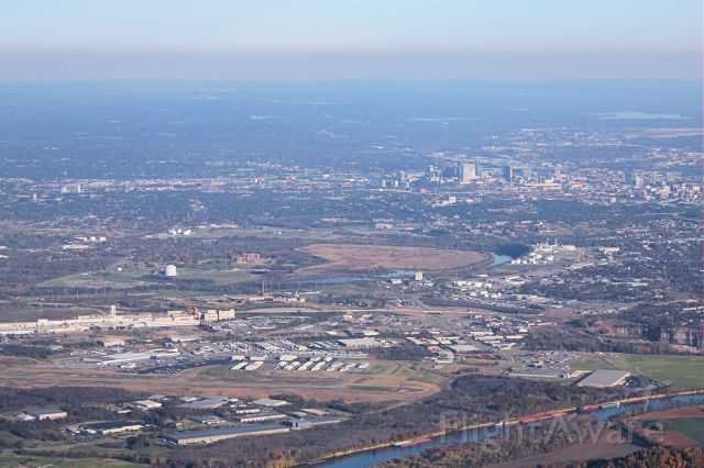 — — - John C. Tune Airport (foreground, lower left), the Cumberland River, and the Nashville skyline.