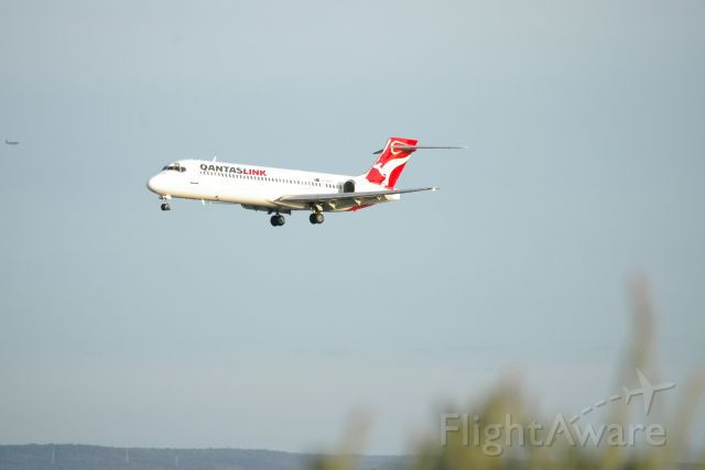 Boeing 717-200 — - Interesting photo of a Qantas Link Boeing 717-200 Landing rwy 03 at Perth Intl Airport with a bush in the frame and another aircraft approach on the edge of the frame. The 717-200 looks like it is looking at a fly.