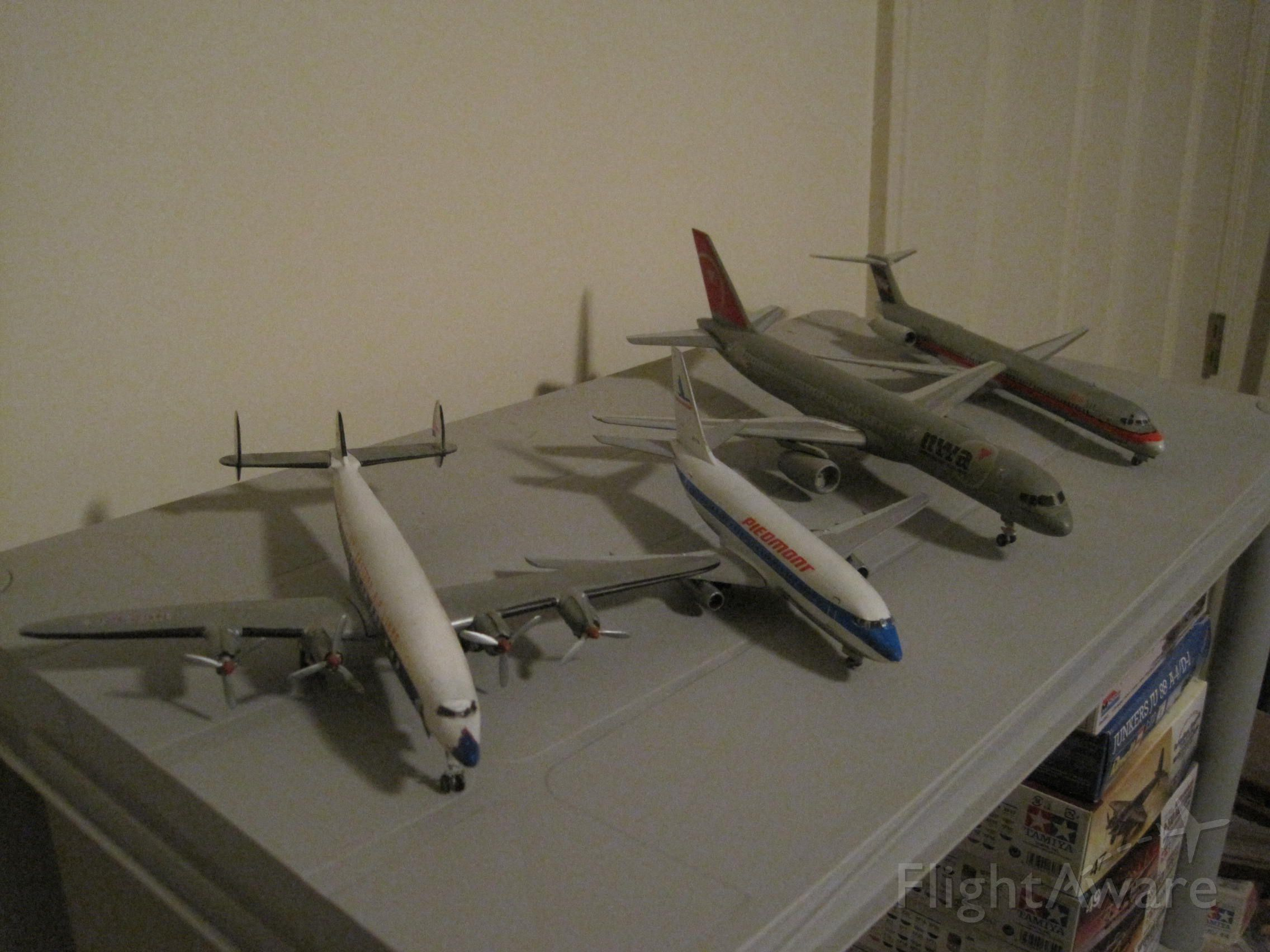 — — - Here are four 1/144 scale model airliners.  A Lockheed Super Constellation in Eastern markings, a Boeing 737-200 in Piedmont colors, a Boeing 757-200 in Northwest markings and a USAir McDonnell-Douglas MD-80.