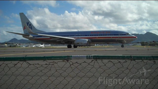 Boeing 737-800 (N975AN) - Princess Juliana International Airport (Airport Beach), A stop during my honey moon cruise. Regretfully, no larger planes were scheduled that day but this did just fine..this is a snap shot of a video I took hanging from the fence. =) I (respectfully) asked my wife if we could go there as soon as the ship docked (on the other side of 'life')...and sure enough, we were the first ones on deck at 0500. A few 'island hoppers' later, I saw this taxiing. I ran over, left hand clenched to fence, right hand with video camera and I patiently awaited being sand blasted and showered with JET A-1 fumes! Obviously, this picture or video don't do this justice, but definitely pretty friggin cool!