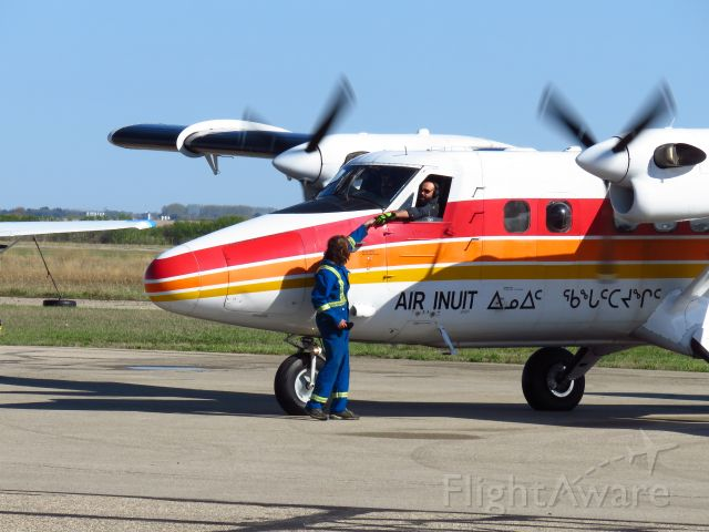 De Havilland Canada Twin Otter (C-FTJJ) - Canada DHC-6-300 Twin Otter makes a rare visit to Yorkton. Here the mechanic is seen retrieving something from the pilot prior to departure.