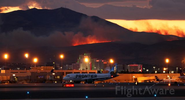 """Airbus A320neo (N307FR) - It was a hot time in Reno last night. This photo, taken just 25 hours ago, catches FFTs """"Champ the Bronco"""" (N307FR) hurriedly trying to taxi from the runway 16R hold line all the way down to the other end in an attempt to make it to runway 34L and get out of town. The Frontier flight had just left the terminal and was almost at the north end of taxiway Alpha, next to go from 16R, when sudden high swirling winds descended from the Sierra Nevada and a vicious electrical storm exploded over the airport and the city. An inbound SW, less than a mile out, encountered a brutal wind sheer and the pilots immediately reported that the flight was diverting to SMF. This Frontier Bus, a Navy C-40, and a FDX heavy all shut down their engines on Alpha to wait out the storm. As they sat, lightning ignited the fire visible here and a second fire just beginning to spread at the right edge of this photo. About 35-40 minutes later, after a UA inbound made a rough arrival on 34L, the FFT pilots requested permission to restart, swap ends of the runway, and get gone for Denver. This pic was taken as they hustled from the hold of 16R to 34L where they made a successful getaway."""