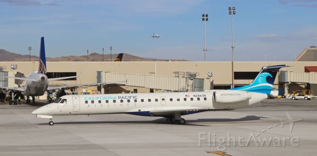 Embraer ERJ-145 (N286SK) - Calfifornia Pacific's N286SK taxies thru the alley to Reno Tahoe International's Gate B2 about twenty minutes after high noon to complete the first half of a KCRQ-KRNO-KCRQ r/trip run. That's a jetBlue Bus, arriving from Long Beach, on approach to 16R in the background.