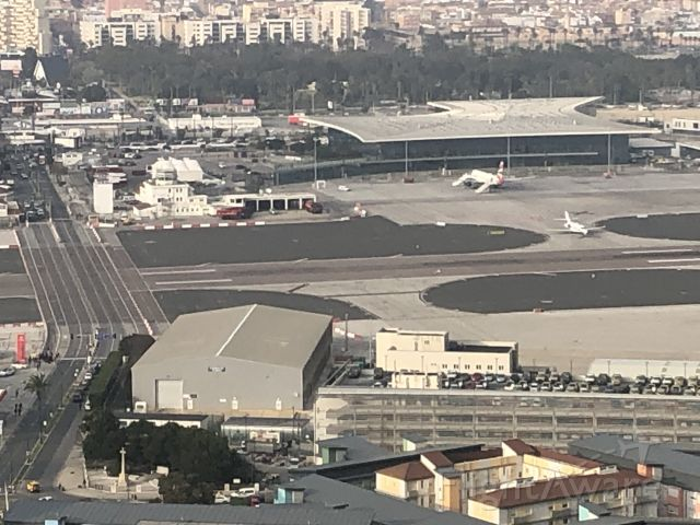 — — - View from the fortress of the runway you walk across to get from Spain into Gibraltar after crossing the border.  You can see the queue of cars/people lining up as the jet enters the runway to back taxi for takeoff.