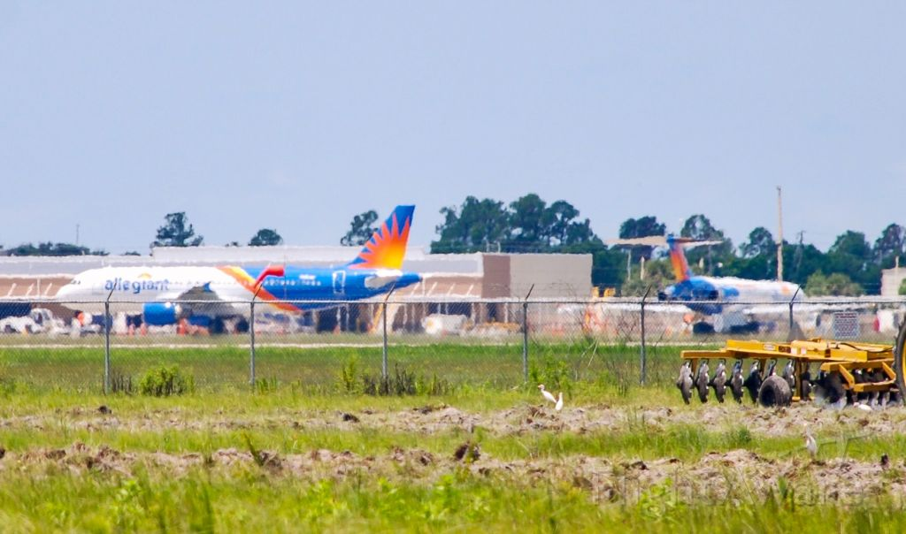 Airbus A320 (N258NV) - View of the ramp from across the field.  Significant because this could be one of the last visits for an Allegiant MD-80 at Punta Gorda!<br />Taken 6/21/18