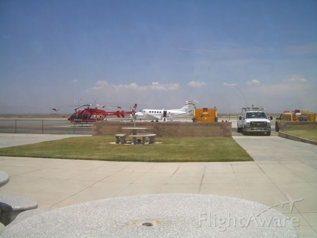 Bell 407 (N48RX) - The AV Hospital helicopter parked beside a King Air at Kwjf  . Picture taken from inside of Foxys Landing Restaurant inside the terminal.