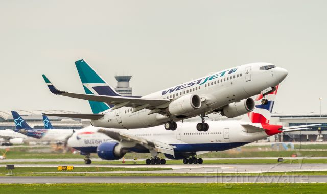 Boeing 737-700 (C-FIWJ) - Westjet 711 gets up and heads to Vancouver as BA93 taxies to the gate in the background