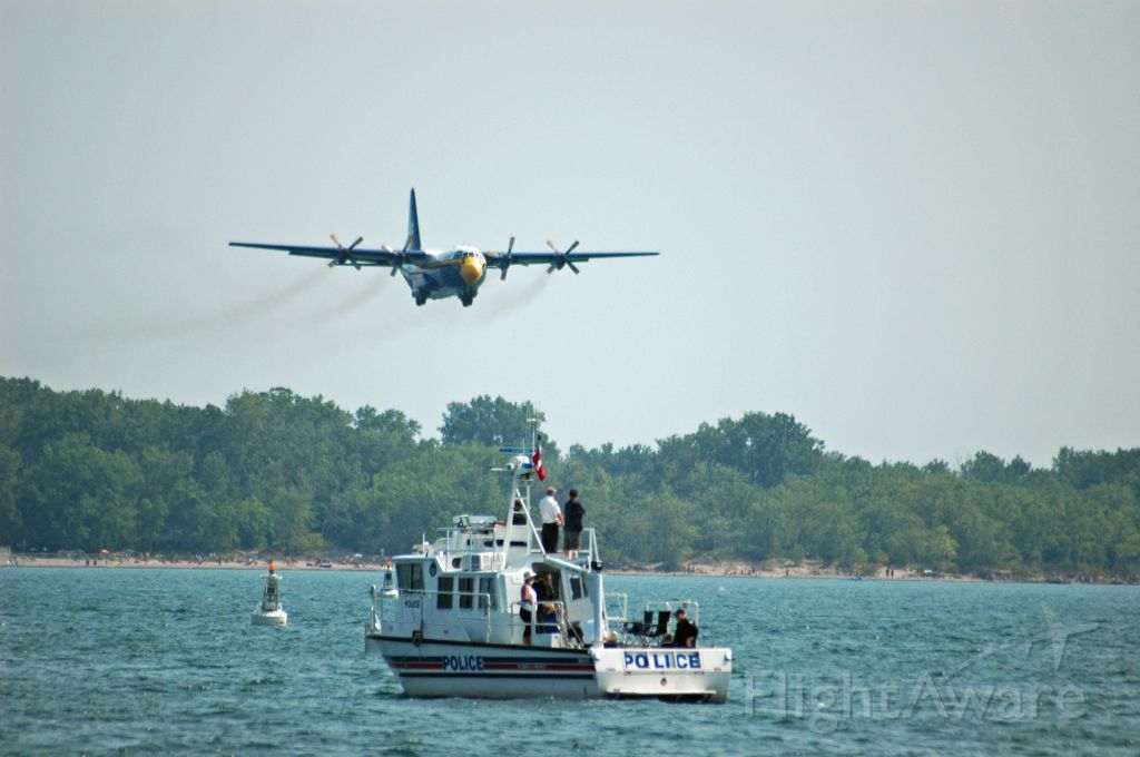 """Lockheed C-130 Hercules — - The Blue Angels C-130 """"Fat Albert"""" (164763) taking off from CYTZ to do its demonstration at the Canadian International Airshow (September 7,2009). Here we have Fat Albert and a Toronto Police boat sharing the spotlight."""
