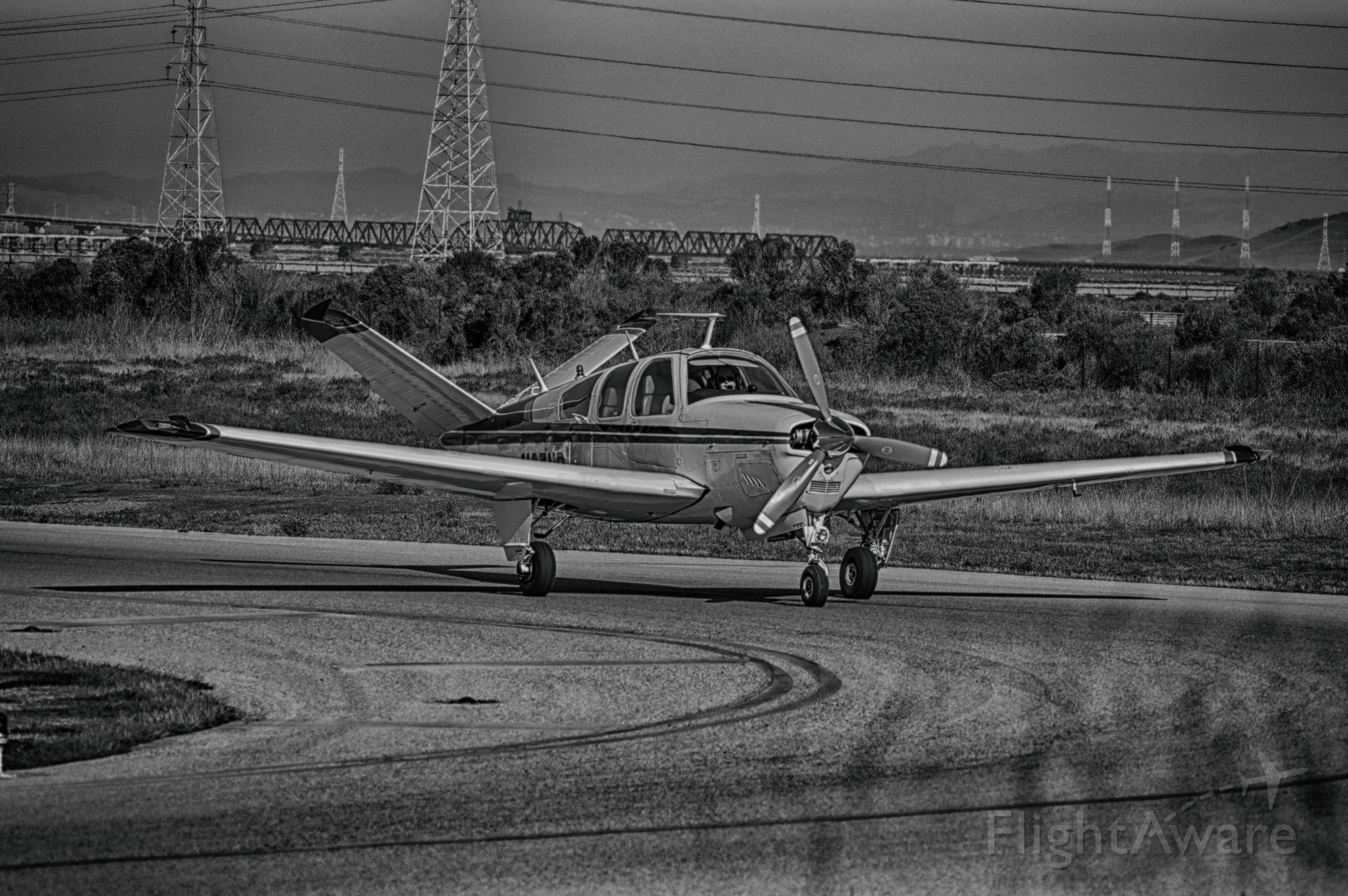 — — - V Tail Bonanza rolling off the runway at KPAO