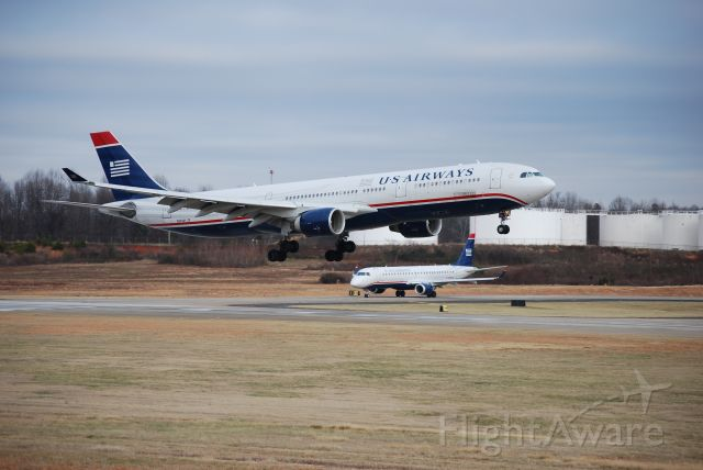 Airbus A330-300 (N270AY) - Landing on runway 18C at Charlotte Douglas International Airport while a US Airways Express E190 (N964UW) holds short - Jan. 2009