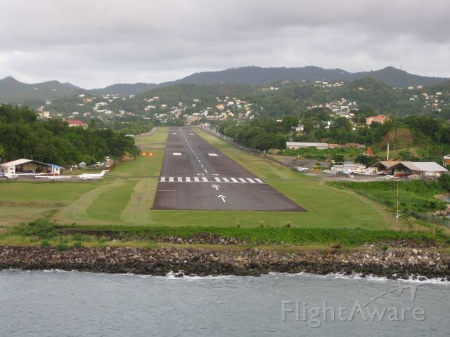 — — - George F. L. Charles Airport, formerly Vigie Airport.(IATA: SLU,ICAO:TLPC) is the smaller of two airports in Saint Lucia, the other being Hewanorra International Airport. It is located 2 km north of Castries, the capital city.    Picture taken from aboard a cruise ship as it left Castries