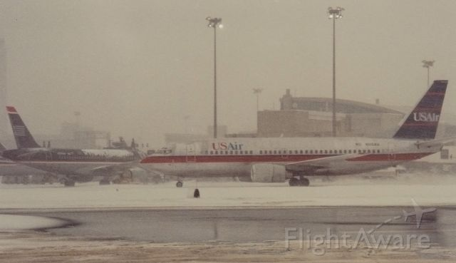 BOEING 737-300 (N515AU) - Not the best conditions for photography-sorry for the result. The big puddle is type 1 and type 4 deicing fluid out at the deice pad. Another day of typical winter ops at BOS -about 2001.