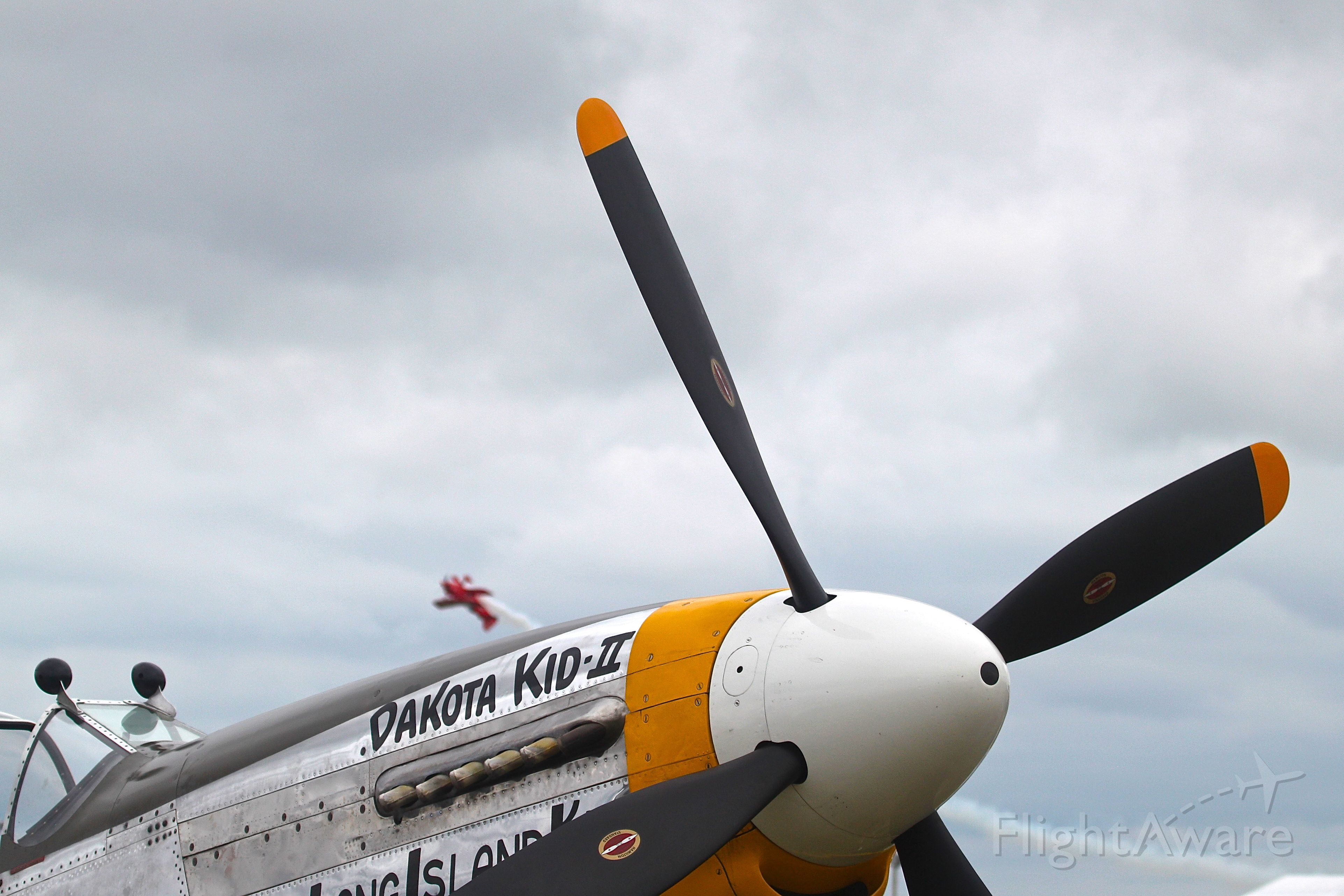North American P-51 Mustang (N151HR) - P-51 parked at Oshkosh while Sean Tucker performs in the background