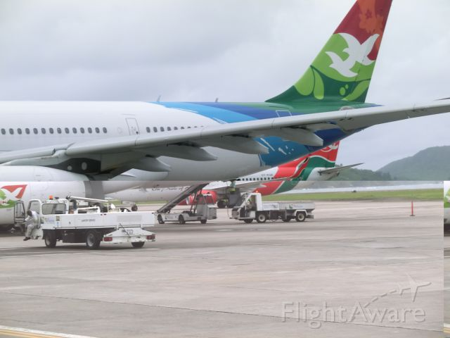 Airbus A330-300 — - A tale of two tails.  Following on from the KQ photo, Air Kenya makes her way behind HM019 Air Seychelles, which had only just arrived a few minutes earlier to the international airport in the Seychelles.