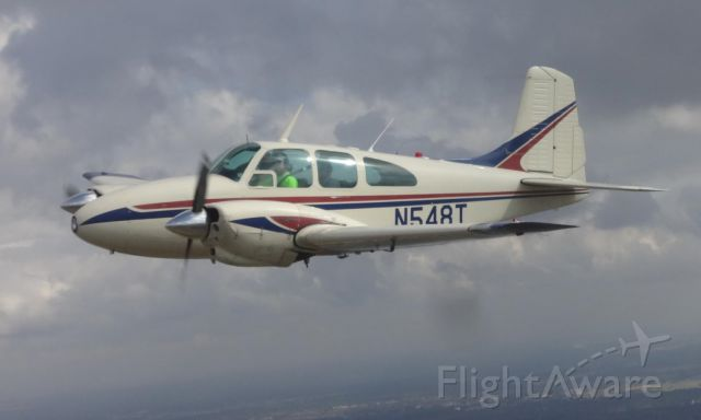 Beechcraft Travel Air (N548T) - Flying off the wing of a Twin Bo