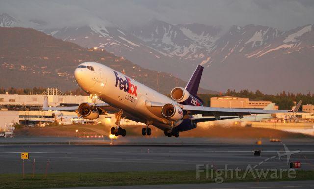Boeing MD-11 (N572FE) - N572FE late evening departure in golden hour light, departing runway 33 in Anchorage, AK.