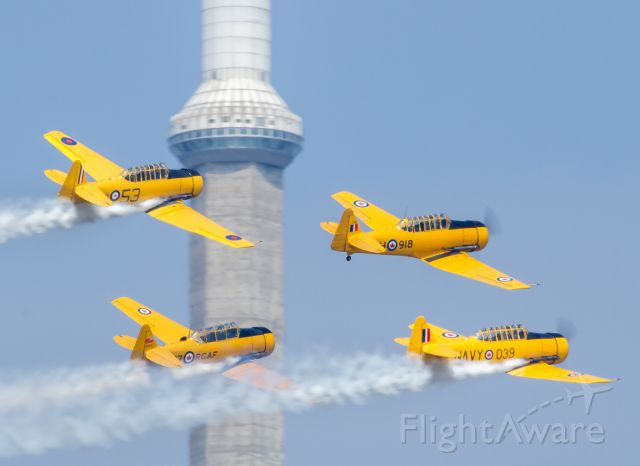 North American T-6 Texan (C-FMKA) - The Canadian Harvard Aerobatic Team fly past the CN Tower on their way back to Billy Bishop Island Airport in Toronto
