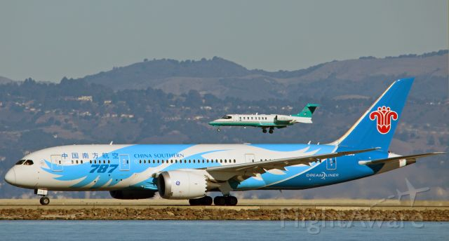 Boeing 787-8 (B-2737) - A Learjet 45(C-FBCL) landing over the China Southern Dreamliner, as it departs