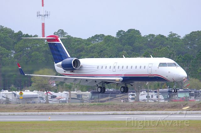Canadair Regional Jet CRJ-200 (N570ML) - Formerly of Mesa Airlines, this Stewart Haas Racing CRJ still wears the base livery of US Airways Express. Seen here landing 7L during the Daytona 500.