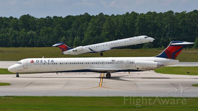 McDonnell Douglas MD-88 (N915DE) - Delta Airlines McDonnell Douglas MD-88 (N915DE) taxis to the gate after arriving at KRDU while in the background Endeavor Air (Delta Connection) Bombardier CRJ-900 (N905XJ) departs KRDU Rwy 5L on 7/29/2017 at 3:21 pm.