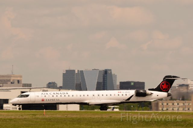 Canadair Regional Jet CRJ-900 (C-GNJZ) - Air Canada CRJ9 departing Regina on its way to Vancouver with city center in the background. Heat waves making it difficult to get a good photo.