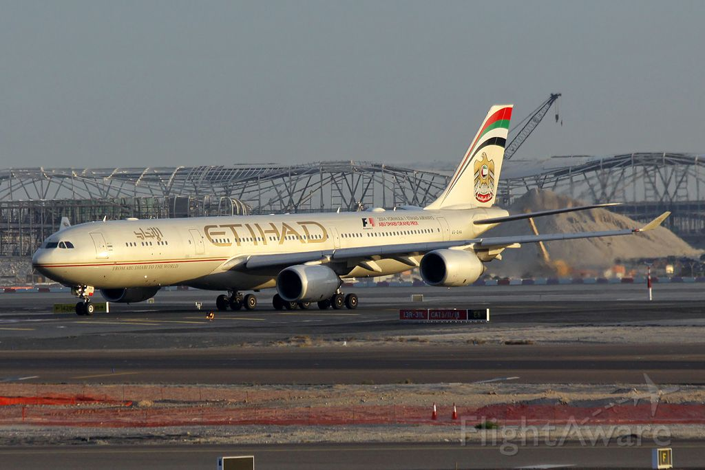 Airbus A340-600 (A6-EHA) - Early morning arrival with the new terminal under construction in the background