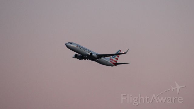 Boeing 737-800 (N878NN) - An evening departure from DFW as seen from Founder's Plaza. Not a lot of light to work with!