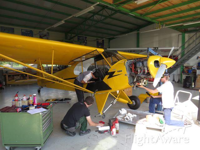 Piper L-21 Super Cub (HB-PDJ) - Maintenance crew working on a Piper PA-18-150 Super Cub at Bex aerodrome, Switzerland.