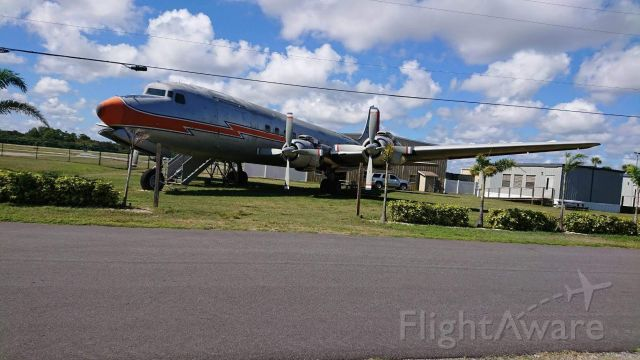 Douglas DC-7 (N381AA) - A classic DC-7 resting outside of New Smyrna Municipal Airport