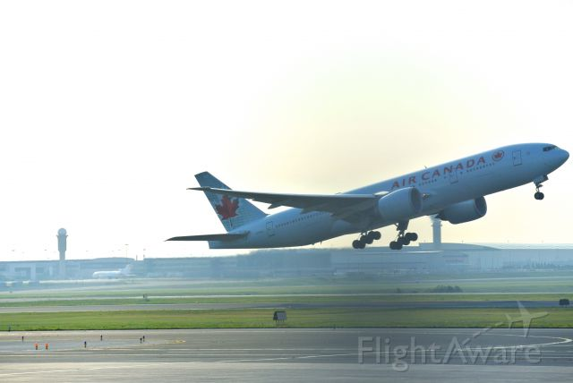 BOEING 777-200LR (C-FIUJ) - Was struggling with the fence this day, but got a couple decent shots